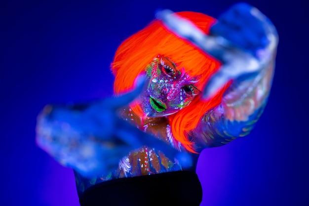 네온 여자 춤. 네온 불빛에 패션 모델 여자, 형광 메이크업으로 아름다운 모델의 초상화, uv에서 포즈를 취하는 여성 디스코 댄서의 예술 디자인, 화려한 메이크업