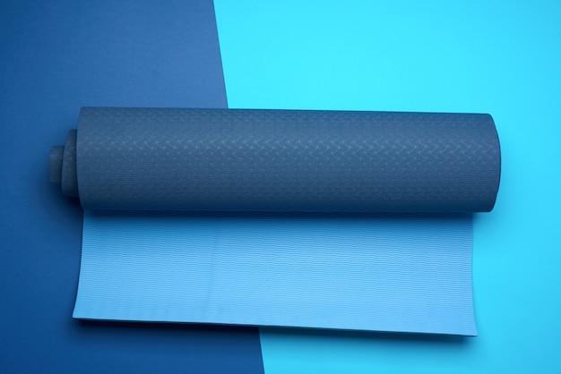 Неопреновый синий витой коврик лежит на синем фоне