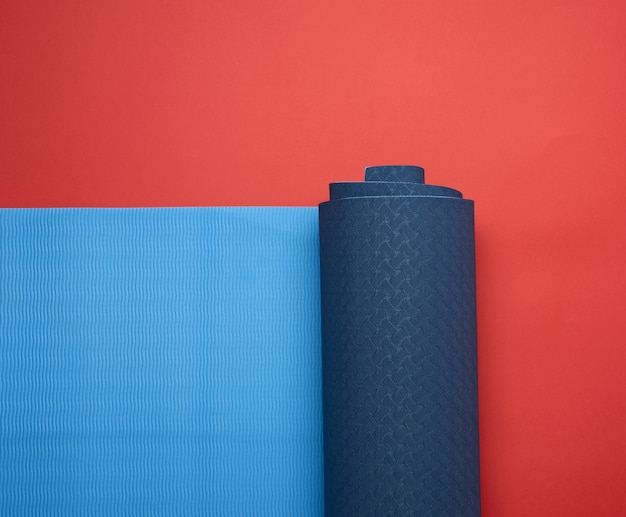 Neoprene blue twisted mat lies on a red background, sports equipment