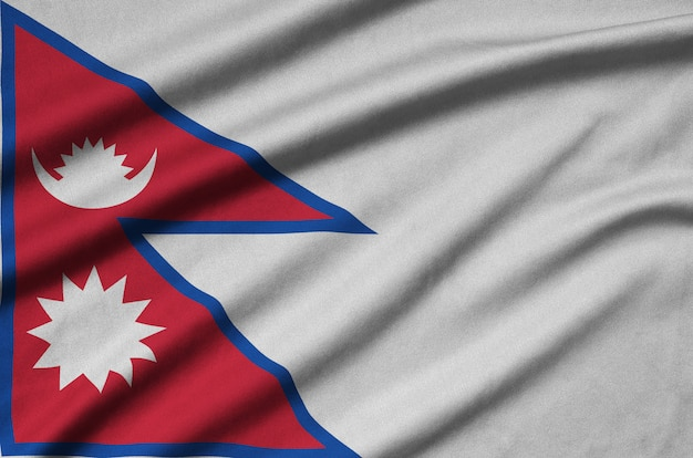 Nepal flag is depicted on a sports cloth fabric with many folds.