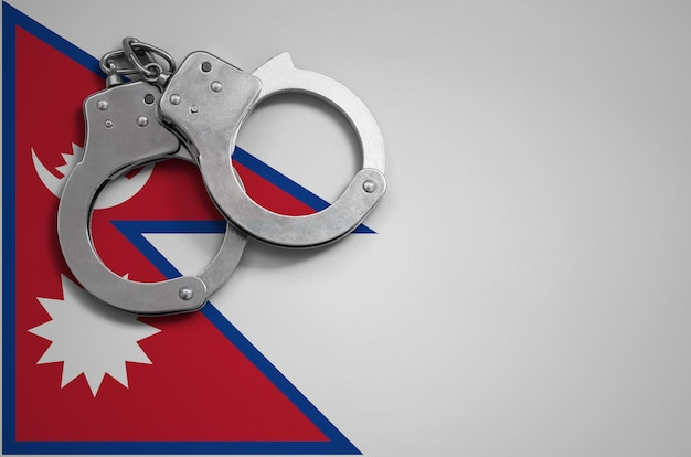 Nepal flag  and police handcuffs. the concept of crime and offenses in the country