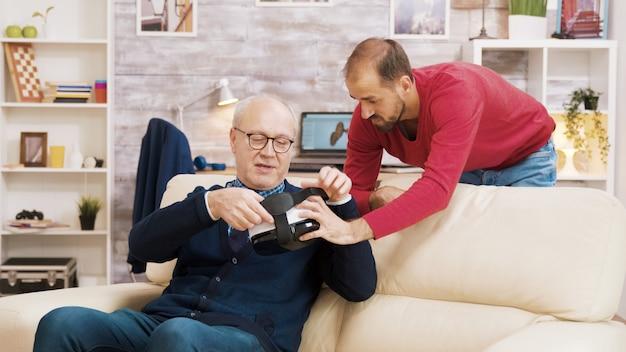 Племянник показывает своему деду, как использовать гарнитуру vr в гостиной.