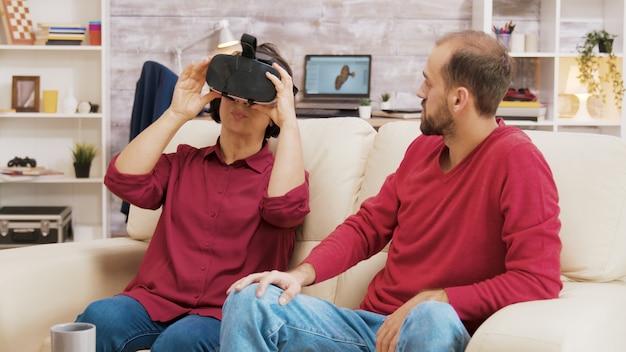Племянник показывает своей бабушке, как использовать очки виртуальной реальности в гостиной.
