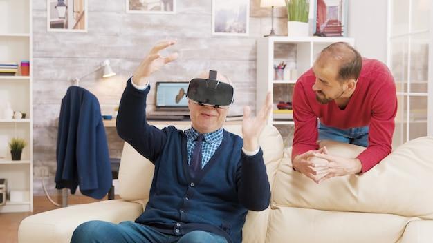 Племянник учит своего деда использовать гарнитуру виртуальной реальности в гостиной.