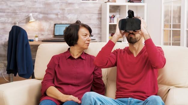 Племянник учит бабушку пользоваться гарнитурой виртуальной реальности в гостиной