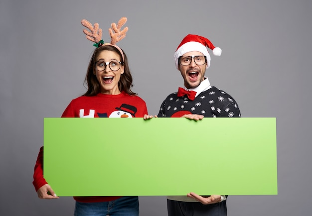 Ботаник пара держит зеленый экран рождественский баннер с копией пространства