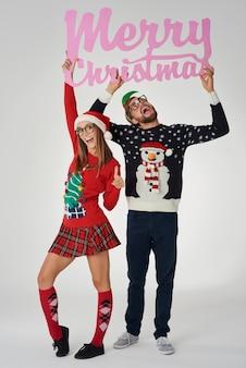 「メリークリスマス」とテキストを保持しているオタクカップル