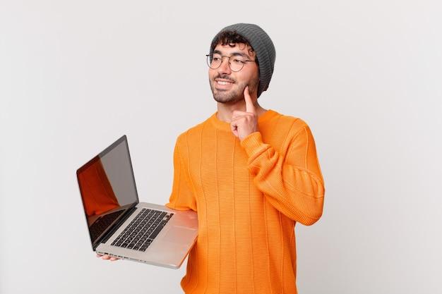 Ботан человек с компьютером счастливо улыбается и мечтает или сомневается, глядя в сторону