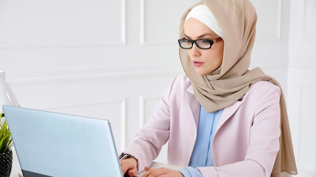 Nerd muslim woman in beige hijab and suit is working on a graduation bachelor project typing on laptop