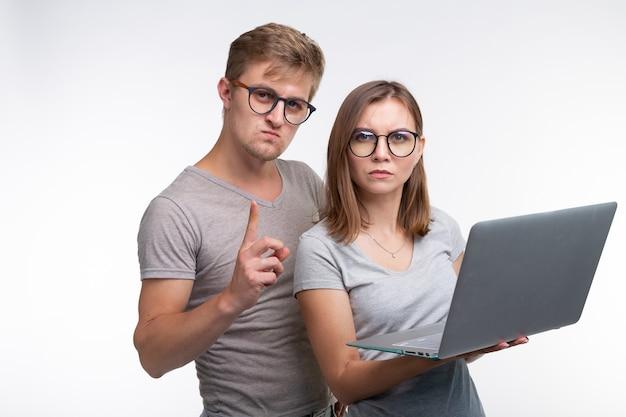 オタク、勉強、人々の概念-ラップトップを持っている学生のカップルは、何かを考えているように見えます。