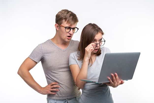 オタク、勉強、人々の概念-数人の学生がネットブックを見て、白い壁に怖がっているように見えます。