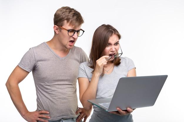Ботаны, учеба, концепция людей. пара студентов смотрят на нетбук и выглядят напуганными на белом.