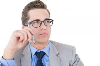 Nerdy businessman holding pen looking away