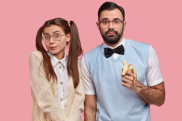 Una coppia nerd vestita con un vecchio vestito alla moda, grandi spettacoli, mangia banana, sembra confusa