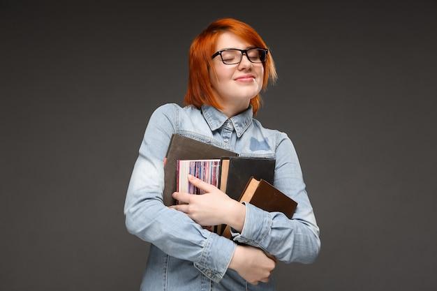 못 난 빨간 머리 여자 학생 책을 들고