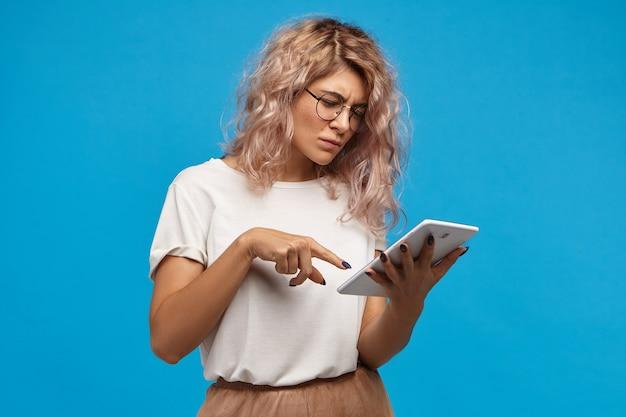 タッチパッドデジタルタブレットでインターネットサーフィン、ソーシャルネットワーク経由で写真をスクロールする丸い眼鏡のオタク深刻なヒップスターの女の子