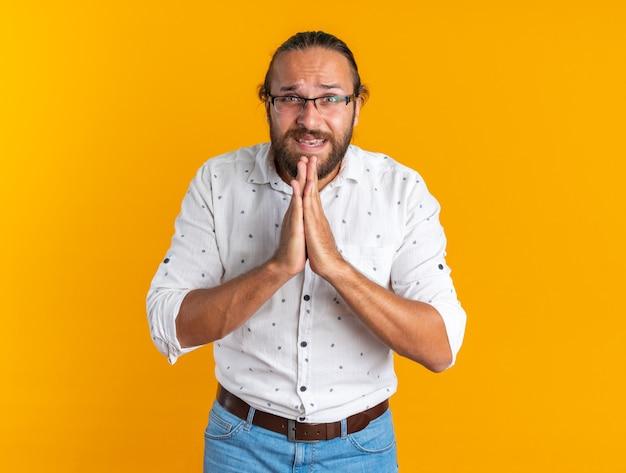 안경을 쓴 긴장한 성인 잘생긴 남자가 주황색 벽에 격리된 채 손을 잡고 기도하는 카메라를 바라보고 있습니다.