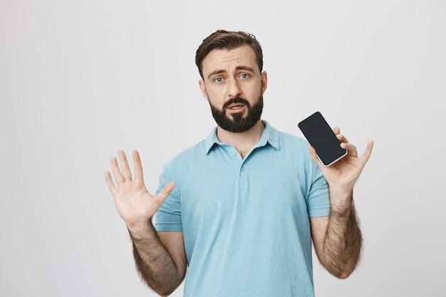 神経質な成人男性の手を上げるとスマートフォンを表示