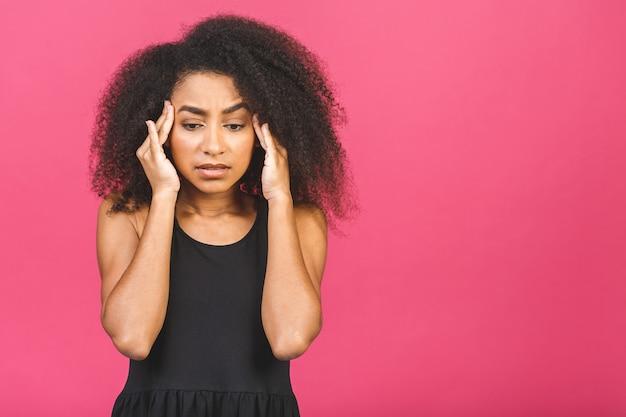 頭痛を和らげたりストレスを緩和したりして呼吸をしているアフリカの神経質な女性、黒い女の子はピンク色に息を吐きながら寺院をマッサージすることを強調しました。