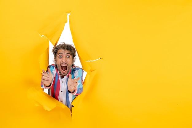 引き裂かれた黄色の紙の穴の背景で神経質で感情的な若い男のポーズ