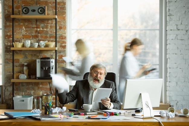 사람들이 흐릿하게 움직이는 동안 바쁜 직장에서 긴장하고 피곤한 상사. 회사원, 관리자는 문제와 기한이 있으며 동료는 산만합니다. 비즈니스, 작업, 워크로드 개념.