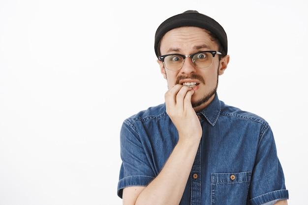 緊張して心配している心配そうな見栄えの良い男性のメガネでひげを生やしたトレンディなビーニーとシャツが下唇に手をかざし、大きな恐ろしい間違いを犯した