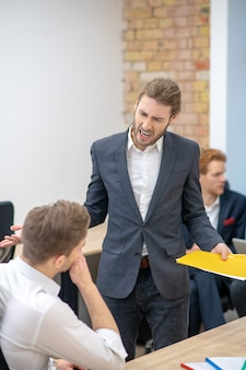 Нервный сердитый человек в темном деловом костюме с документами в руке кричит, жестикулируя на сотрудника