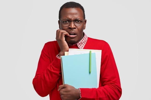 神経質な不安な暗い肌の男は指を噛み、激しく見え、教科書を持って、不快に眉をひそめ、赤いセーターを着て、エレガントなシャツを着ています