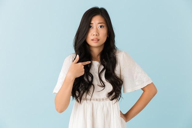 Нервная азиатская красивая женщина изолирована над голубой стеной указывая