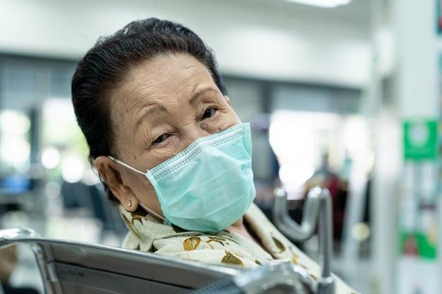 政府の病院で医師に会うのを待っている神経質なアジアの80歳の高齢女性。