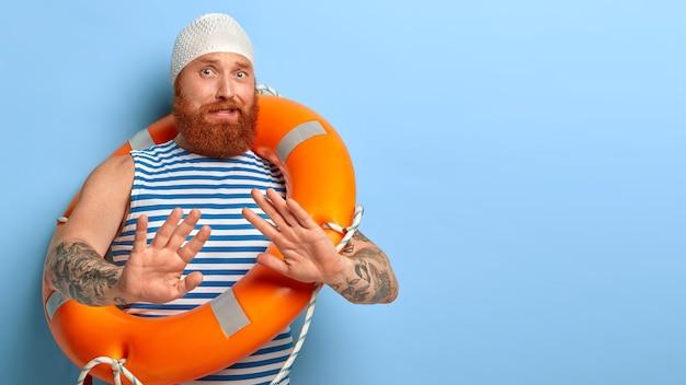 Нервный бородатый рыжий парень делает отказный жест, вытянутые ладонями боится плавать без посторонней помощи, учится плавать, носит непромокаемый головной убор, полосатый жилет несет оранжевый надутый спасательный круг