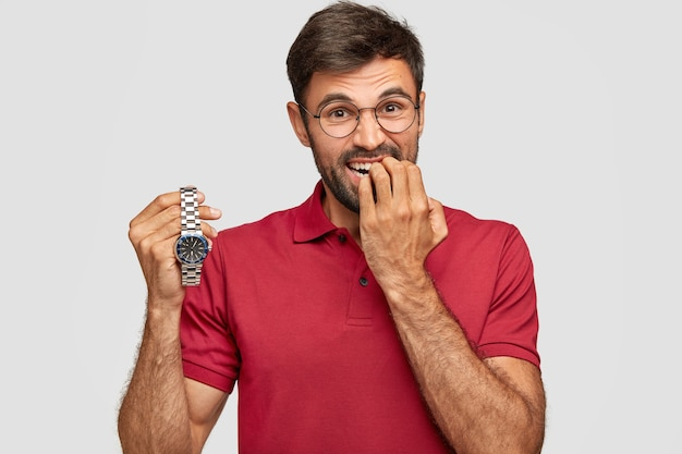Nervous bearded male bites finger nails, holds wrist watch, worries as being late for important meeting, dressed in casual t-shirt. embarrassed young man waits for something. times flies quickly