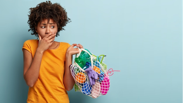 Nervous black woman with curly hair, covers mouth, looks worried at bag of plastic trash, shows negative emotions, takes part in ecology campaign against environmental pollution. socail work