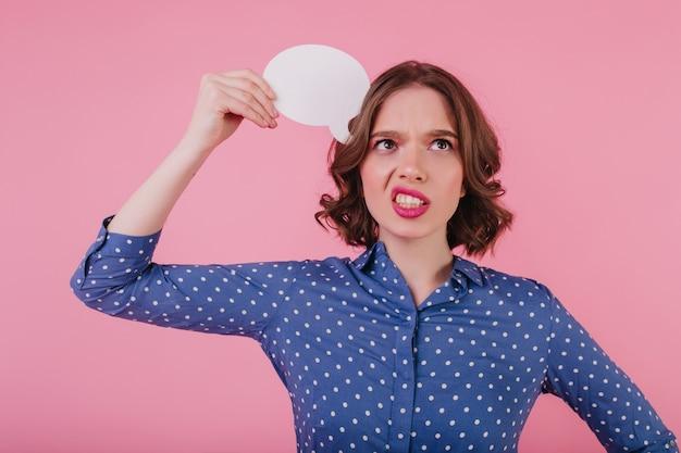 ピンクの壁に立っている青い服装の神経質なブルネットの女性。何かを考えて見上げる心配している白人の女の子。
