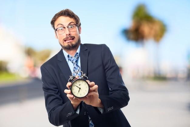 Nervous businessman showing a clock