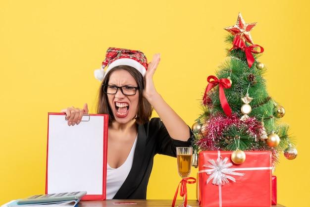 サンタクロースの帽子と眼鏡でスーツを着た神経質な魅力的な女性がオフィスでドキュメントを表示