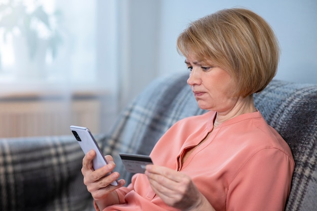 Nervous confused elderly senior woman, stressed worried sad frustrated lady having problem with paying, buying online, payments with credit blocked bank card, mobile phone, smartphone. internet fraud