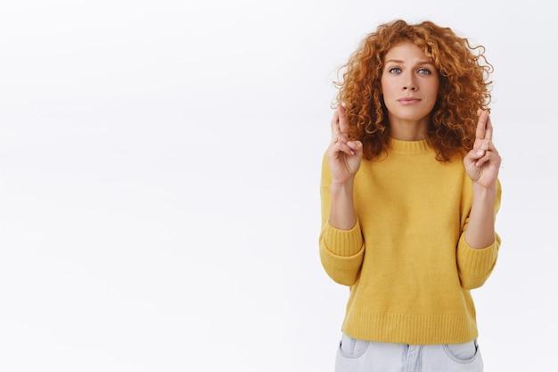 Нервная милая глупая рыжая кавказская женщина с вьющимися волосами, прикусывает губу и смотрит в камеру с надеждой, скрестив пальцы, удачи, молится и ждет объявления результатов, хочет победы, белая стена