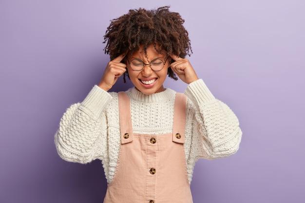 神経質な暗い肌の女性は、ストレスを管理し、痛みを和らげ、こめかみに前指を置き、顔を笑い、紫色の壁に隔離されたスタイリッシュな服を着ます。否定的な感情と片頭痛の概念