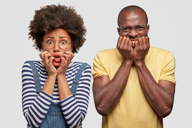 神経質な暗い肌の女性と男性は心配そうに見え、手を口の近くに保ち、ひどい何かに気づき、カジュアルな服を着て、白い壁に隔離されます。驚いた家族のカップルは神経質に見えます