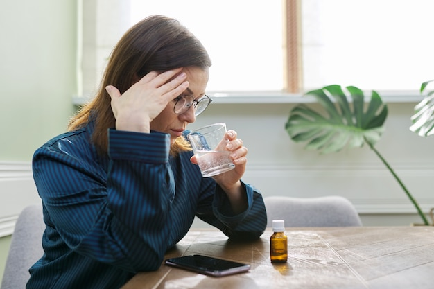 Нервное расстройство, депрессия, нервозность, возрастные проблемы со здоровьем. зрелая женщина капает капли со стаканом воды, пьет успокоительное, дома в пижаме, копией пространства