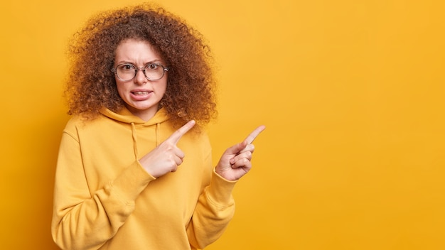 Nervous displeased curly haired woman frowns face says its unfair points at upper right corner with dislike expression complains about something bad wears glasses sweatshirt isolated on yellow wall
