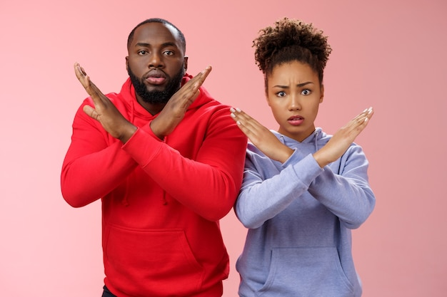 Nervous displeased two african-american man woman asking friend tell they absent not here show cross signs frowning disturbed worried begging not tell quit, stop standing pink background