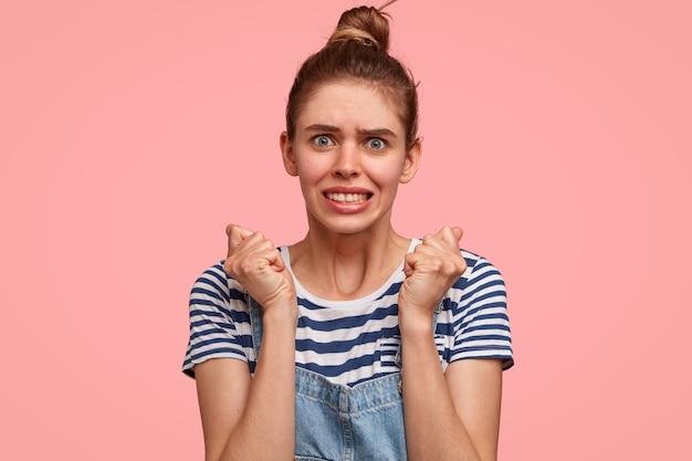 神経質な不機嫌な女性は拳で手を押し続け、歯を食いしばり、絶望的な表情をしています