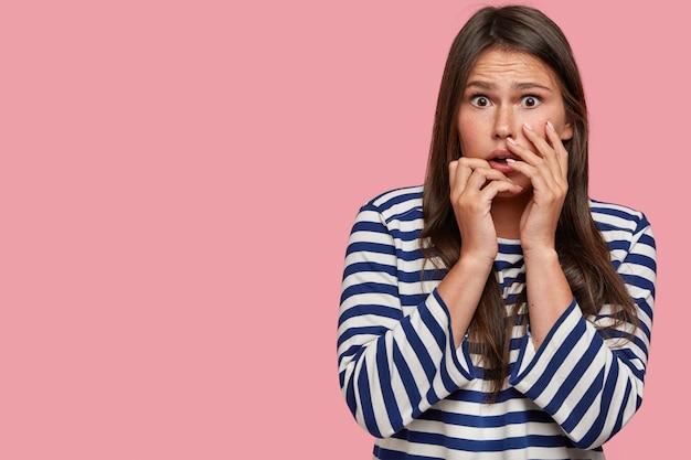 La ragazza nervosa e imbarazzata guarda con un'espressione spaventata