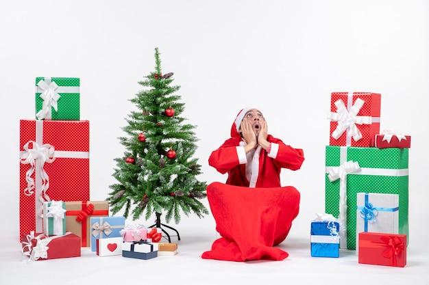 Нервный эмоциональный молодой человек, одетый как санта-клаус с подарками и украшенной елкой, сидит на земле и смотрит вверх на белом фоне