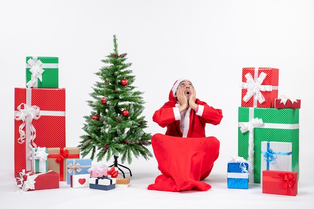Nervous emotional young adult dressed as santa claus with gifts and decorated christmas tree sitting on the ground looking above on white background