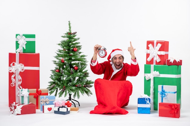 Nervous excited santa claus sitting on the ground and raising clock near gifts and decorated xmas tree on white background