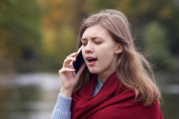 긴장 좌절 화가 젊은 여자, 휴대 휴대 전화로 이야기하는 짜증 소녀, 스마트 폰에 부정적인 대화를 나누고, 비명