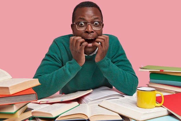 Nervous frustrated black student looks with worried expression, keeps hands near opened mouth, surrounded with opened textbook